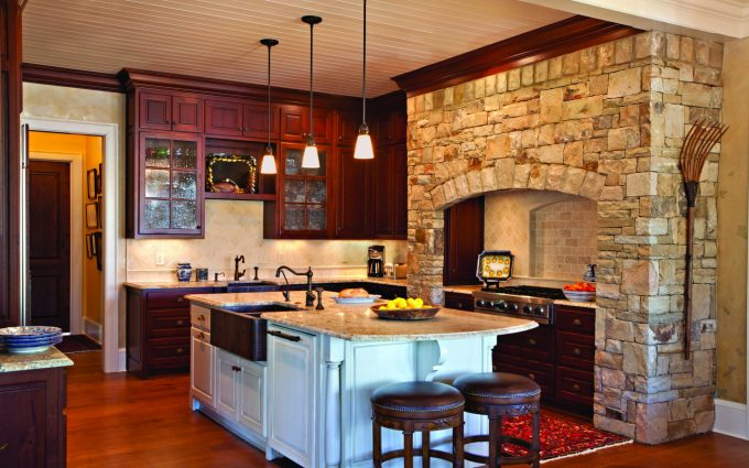 The beautiful kitchen in this Georgia lake house includes a stone hearth designed by Boston Interior Designer Elizabeth Swartz Interiors.