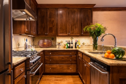 The kitchen of a Boston brownstone with interior design by Elizabeth Swartz Interiors is renovated in the traditional style with polished finishes and traditional furnishings, honoring its historic Boston roots.