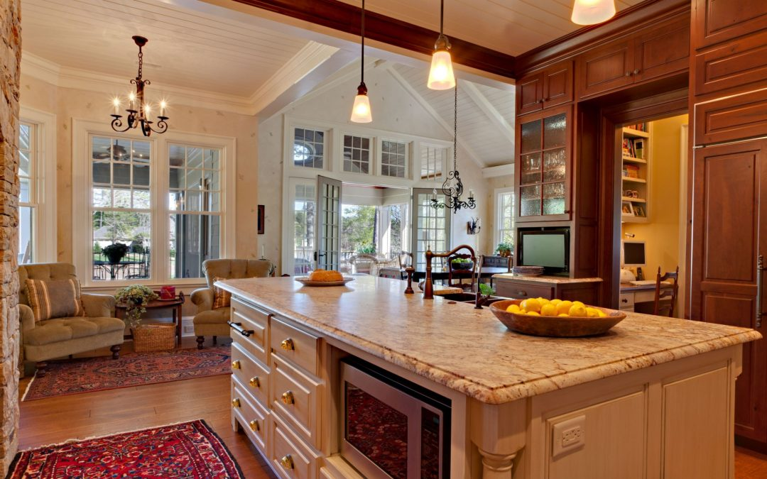 Looking from the kitchen through the dining room and out to a main floor screened porch you can see the vaulted ceilings and large windows in each room designed by Boston Interior Designer Elizabeth Swartz Interiors.
