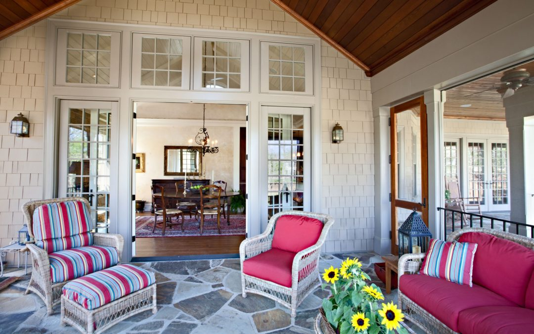 An screened porch on the main level designed by Boston interior designer Elizabeth Swartz Interiors offers a place to gather for conversation or entertaining.