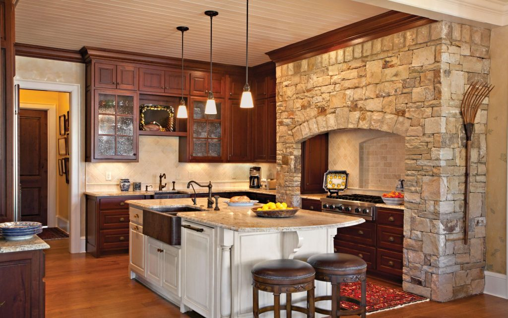 A centrally located large kitchen includes a large island and a stone hearth around the stove in this beautiful kitchen designed by Boston Interior Designer Elizabeth Swartz Interiors.