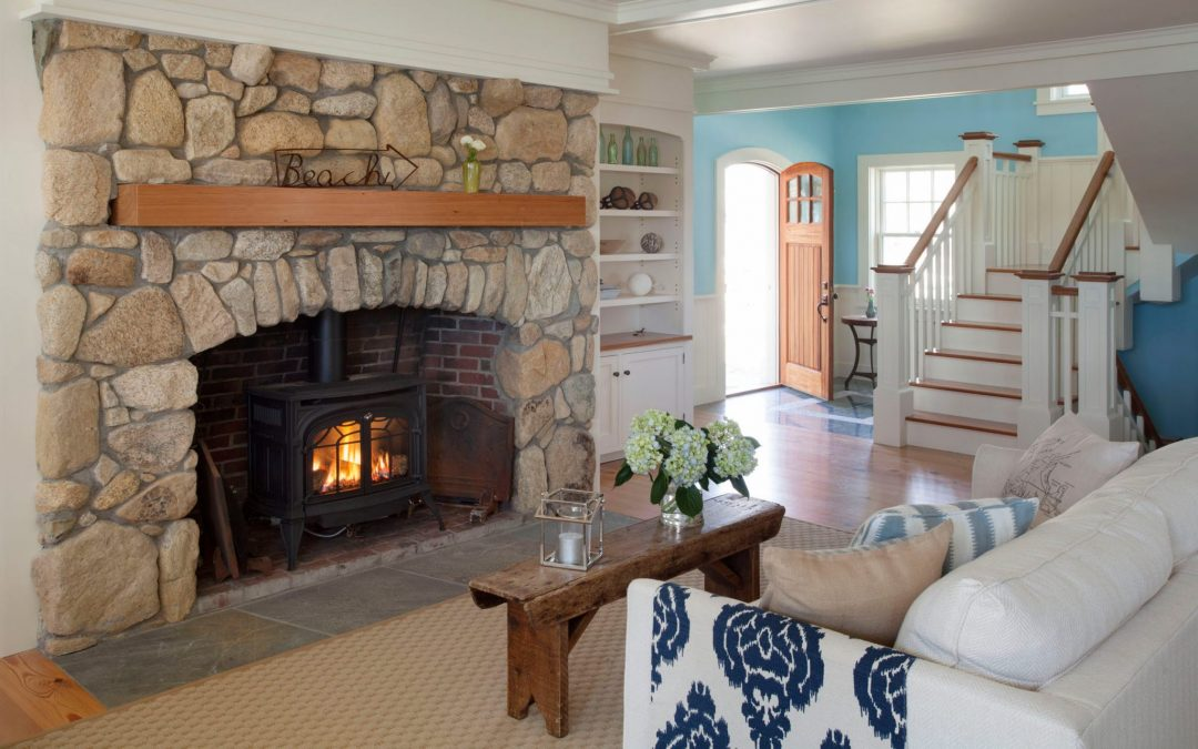 The interior design of the living room in this beach cottage on Martha's Vineyard by Boston Interior Designer Elizabeth Swartz Interiors features cool blues, warm woods and a fieldstone fireplace, reflecting the home's island roots.