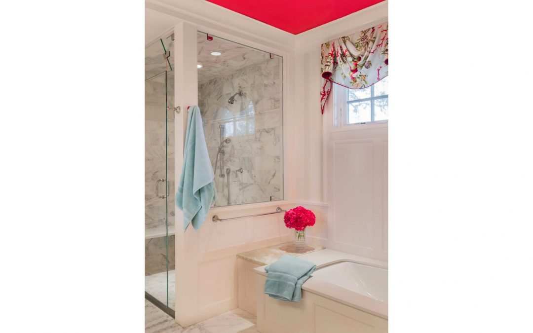 The master bath of this contemporary coastal home designed by Boston Interior Designer Elizabeth Swartz Interiors features custom window treatments that tie the bold pink ceiling to the cool blue linens.