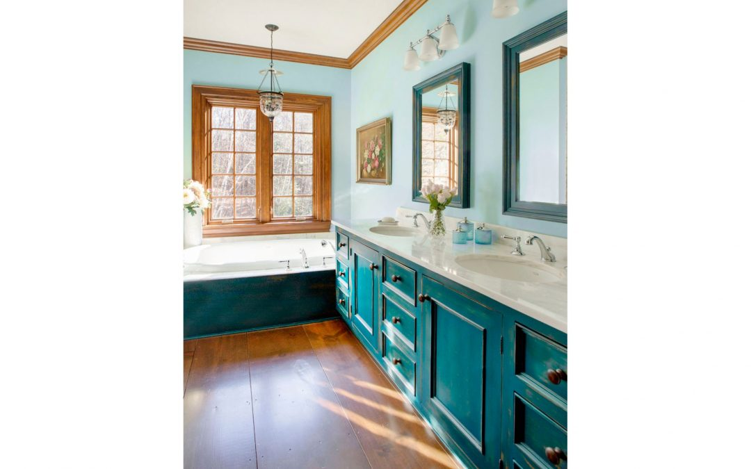The master bathroom of this Vermont farmhouse by Boston Interior Designer Elizabeth Swartz Interiors combines contemporary design elements with traditional architectural details, custom cabinetry, rich colors and local materials.