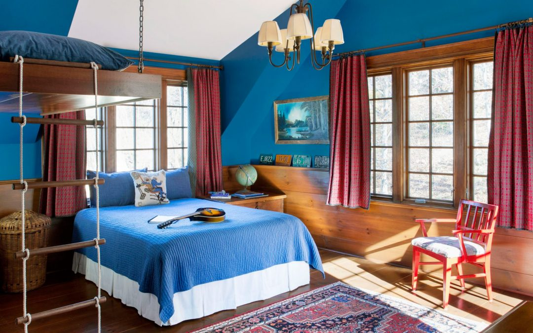 An additional bedroom in this Vermont family farmhouse by Boston Interior Designer Elizabeth Swartz Interiors combines contemporary design elements with traditional architectural details, rich colors and local materials.