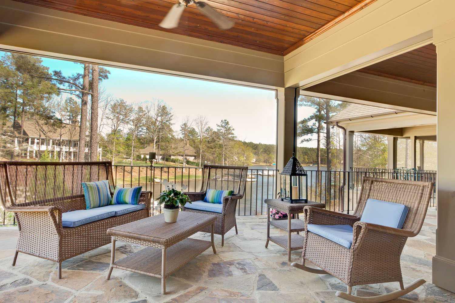 In this porch off a master suite makes living outdoors easy with retractable screens that can be put in place to protect the couple from insects, or on bugless days be opened to allow unobstructed views.