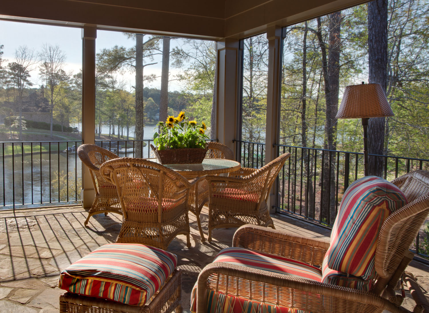 Boston interior designer Elizabeth Swartz Interiors helps to take the indoor living outdoors with the use of indoor lamps and other furnishings on this covered porch.
