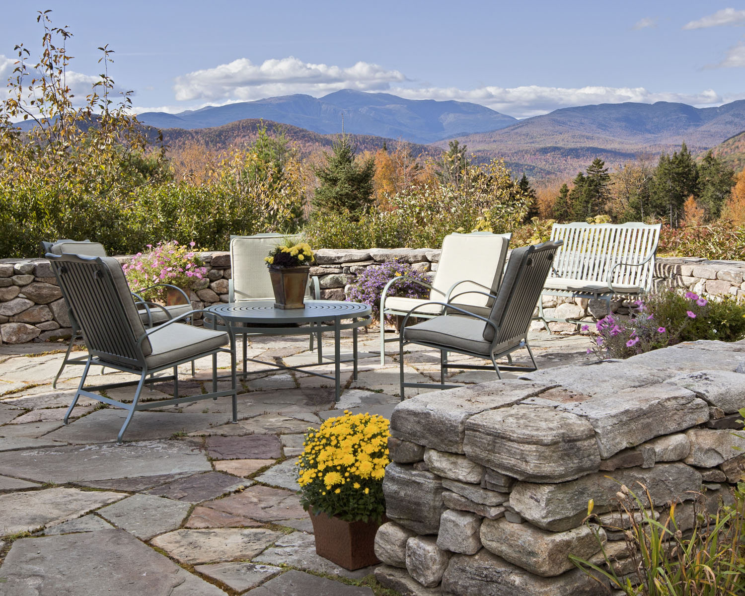 This space designed for living outdoors in the White Mountains was designed by Boston interior designer Elizabeth Swartz Interiors utilizing a short stone wall to define the space.